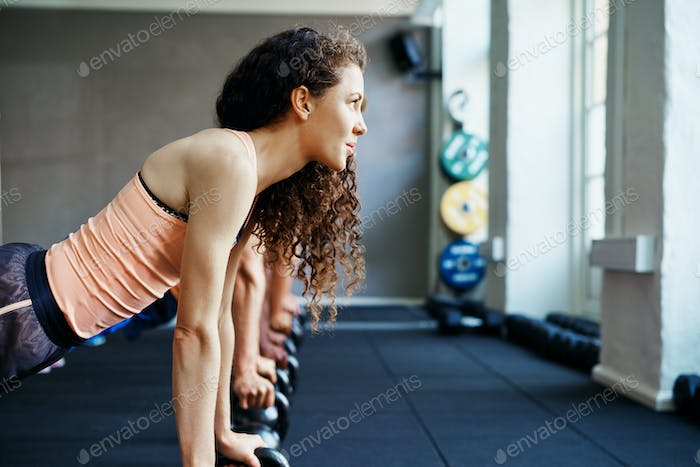 Focused woman doing pushups on weights in a gym class