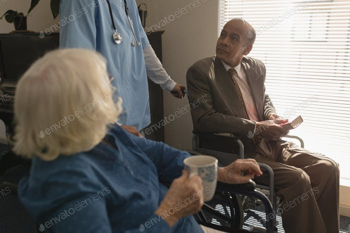 Side view of disable senior couple talking and listening with doctor at home