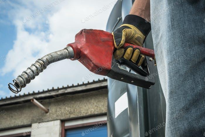 Men Hold Diesel Pump Nozzle in His Hand