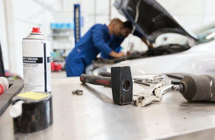 working tools and men repairing car at workshop