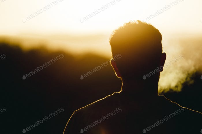 Silhouette of man smoking and watching the orange sun set