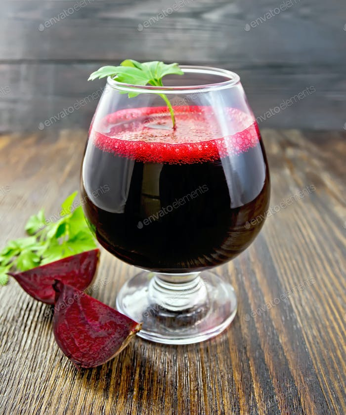 Juice beet in wineglass on dark board