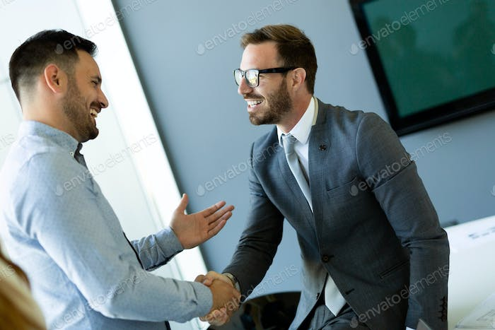 businesss and office concept - two businessmen shaking hands in office