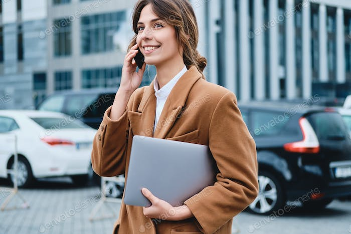 Young positive businesswoman in coat with laptop happily talking on cellphone on city street