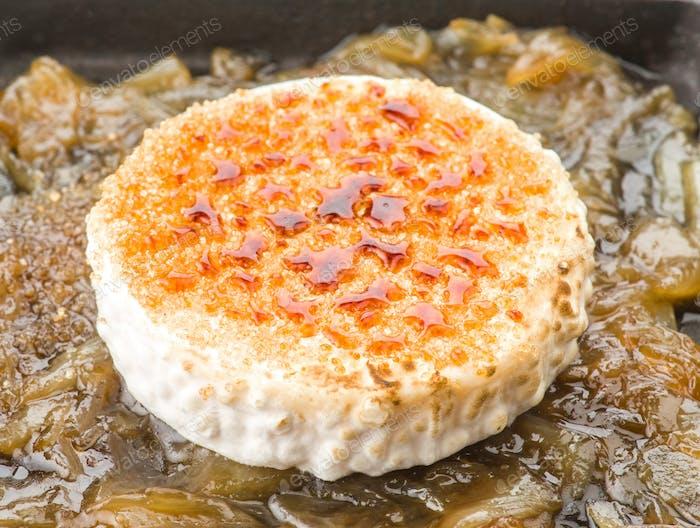 Scheibe Ziegenkäse auf karamellisierte Zwiebel auf Eisenpfanne