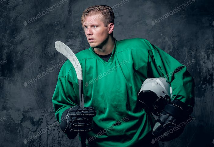 Hockey player holds protective helmet and playing stick on grey