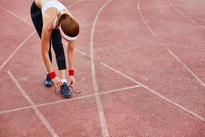 Tying shoelace at stadium