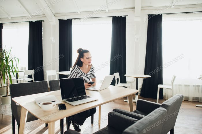 Young attractive woman looking away thoughtfully with her laptop opened.