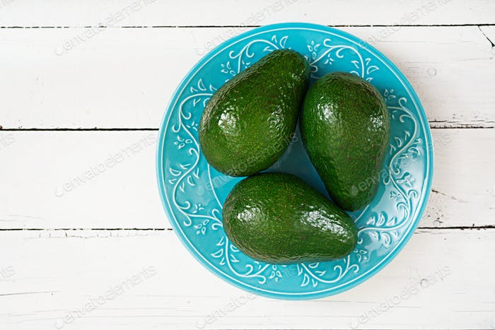 Three ripe avocados on a wooden table. Healthy food concept. Top