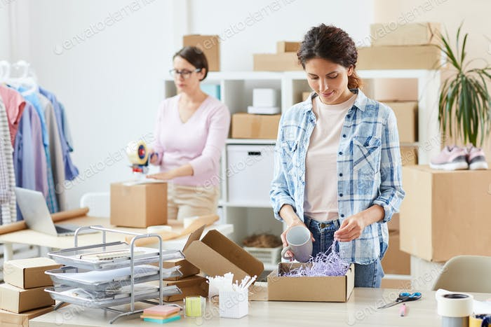 Pretty young manager of online shop packing mug in carton box