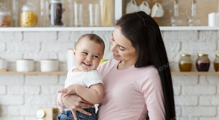 Cheerful mother holding her laughing baby at kitchen