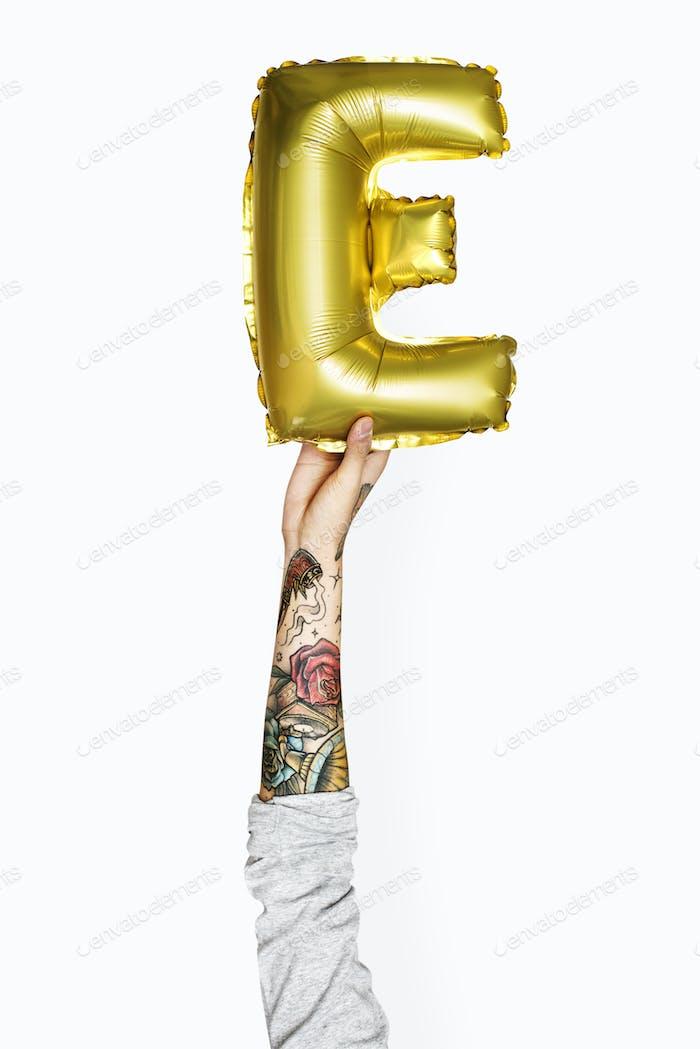 Hand holding an alphabet E balloon