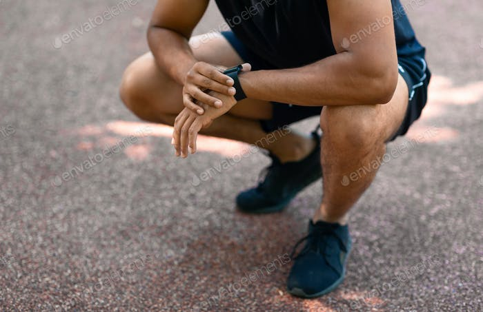 Close up view of young black jogger checking smartwatch during his morning workout