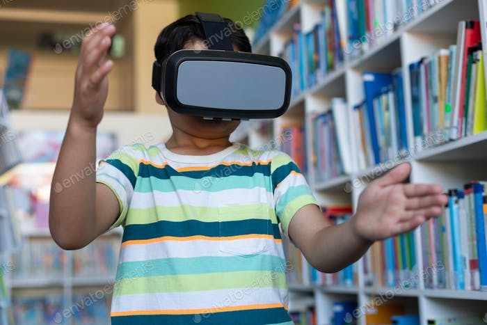 Schuljunge mit einem Virtual Reality Headset in einer Bibliothek in der Grundschule