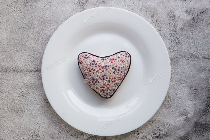 Red heart on plate on wooden background.