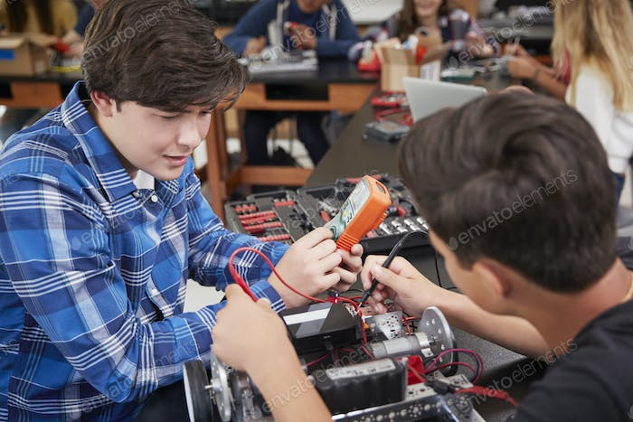 Two Male Pupils Building Robotic Vehicle In Science Lesson