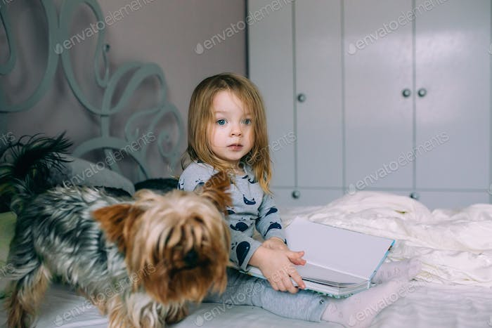 Little girl sitting in bed