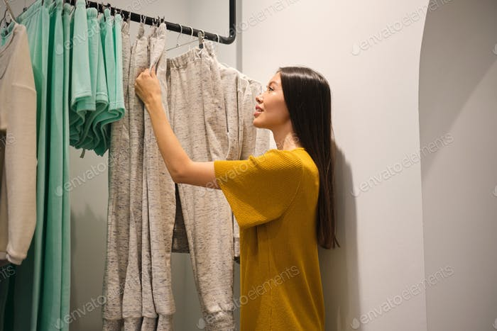 Beautiful casual Asian girl happily choosing clothes in fashion store