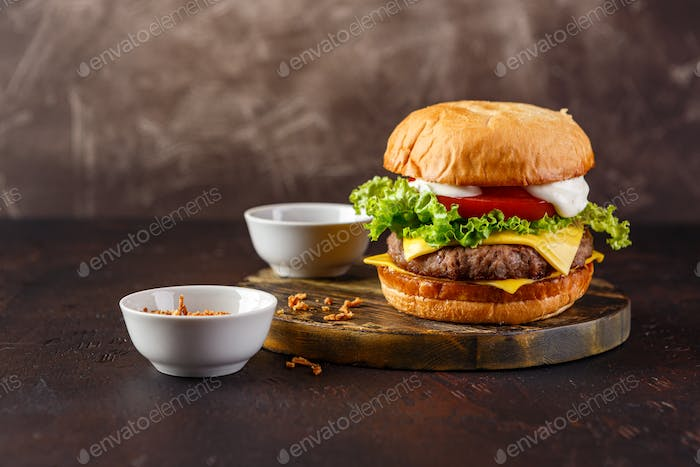 Close-up of home made tasty burger on wooden table.