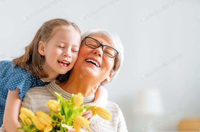 Abuela y chica sonriendo y abrazando