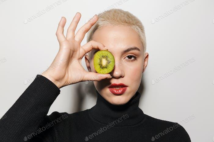 Blonde stylish woman holding kiwi covering eye.
