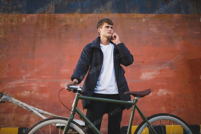 Boy with brown hair standing with bicycle and dreamily looking aside while talking on his cellphone