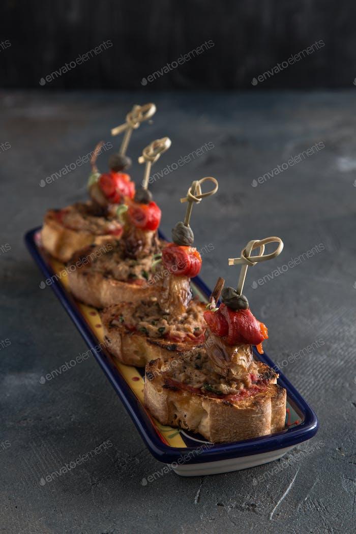 Thunfisch-Tapenade auf leicht geröstetem Baguette mit Pfeffer, Zwiebel und Kapern