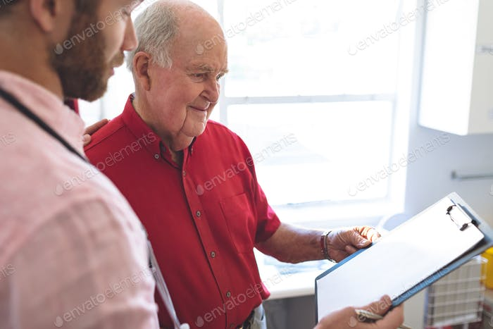 Side view of Caucasian male doctor showing medical report to Caucasian senior patient in clinic
