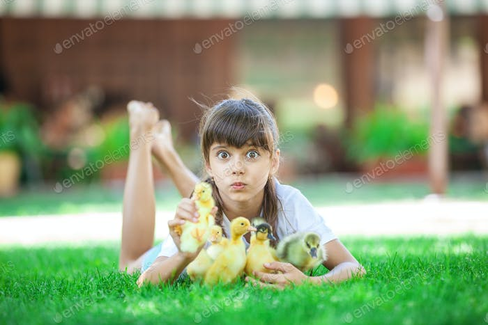 Cute girl lying on grass and holding spring ducklings