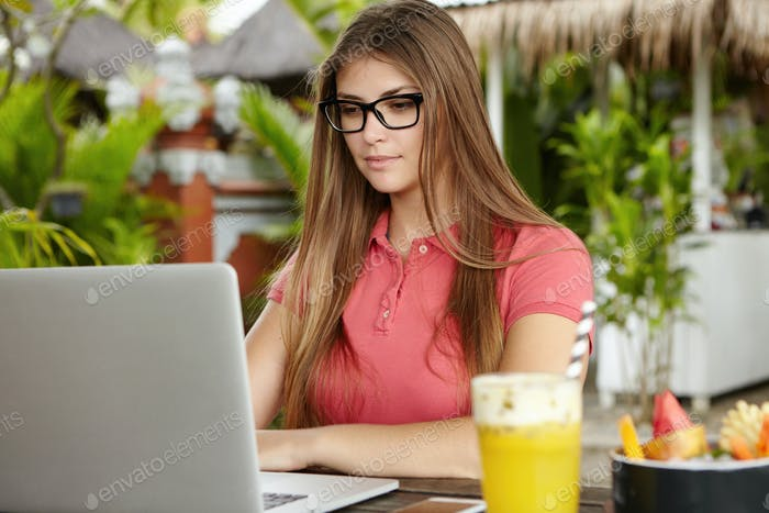 Ernsthafte und selbstbewusste Freiberuflerin trägt rechteckige Brille mit Laptop für Remote-Arbeit