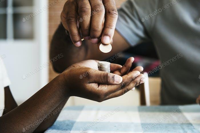 Papá le da monedas a su hija