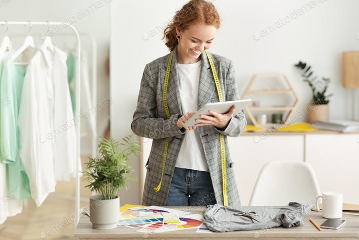 Fashion designer browsing new sketches collection on tablet