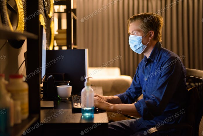 Young businessman with mask working from home late at night