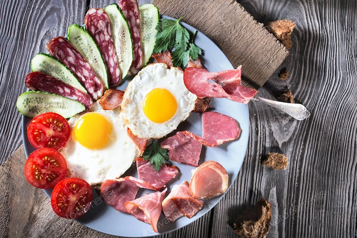 Fried eggs with bacon and vegetables on a wooden table