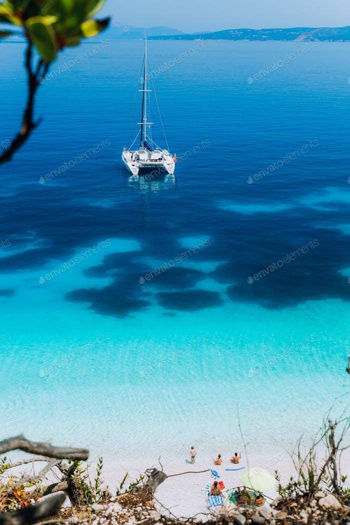 Weiße Katamaranyacht vor Anker auf klarer azurblauer Oberfläche mit dunklem Muster in ruhiger blauer Lagune
