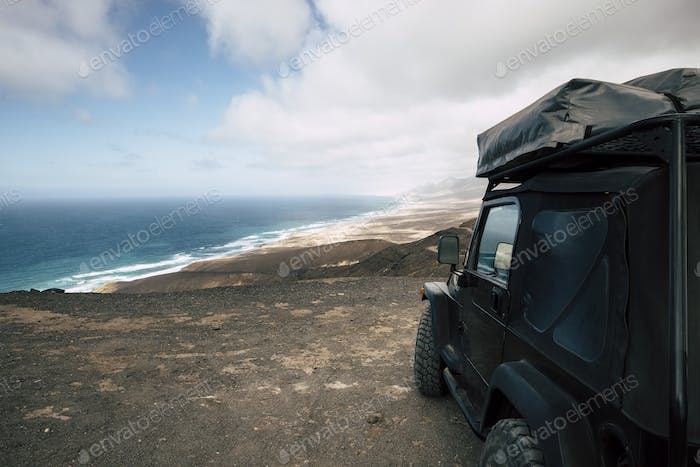 Black off road car parked on the top of a valley