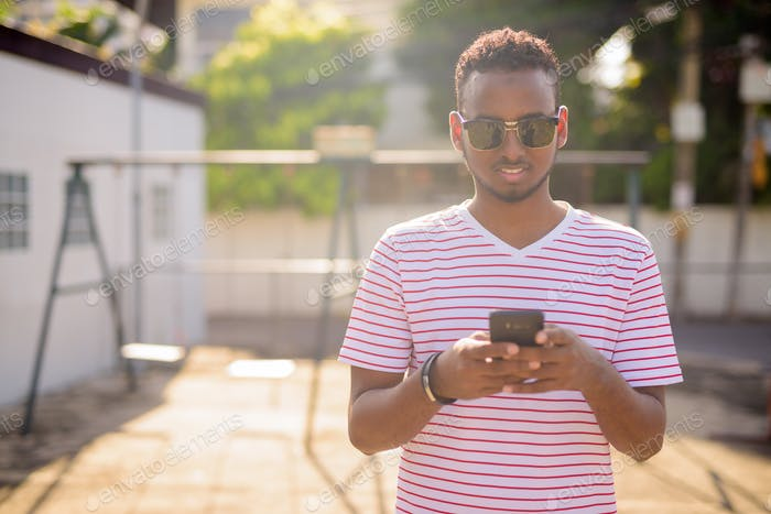 Happy young African bearded man with sunglasses using phone outdoors