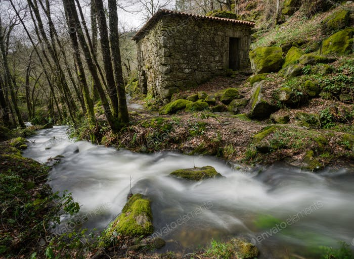 Ländliches Steinhaus neben einem Bach