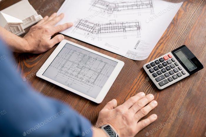 Hände des modernen Ingenieurs lehnte sich auf Holztisch beim Biegen über Tablette