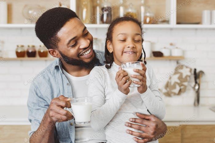 Padre africano animando a la hija a beber leche