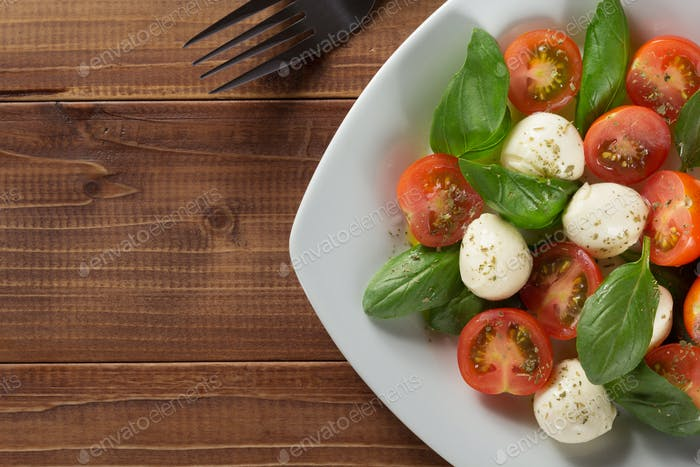caprese salad in plate at wood
