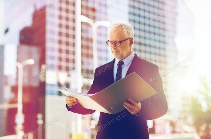 senior businessman with ring binder folder in city