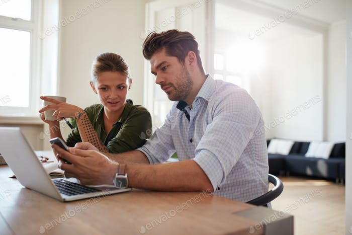 Young couple at home using smart phone