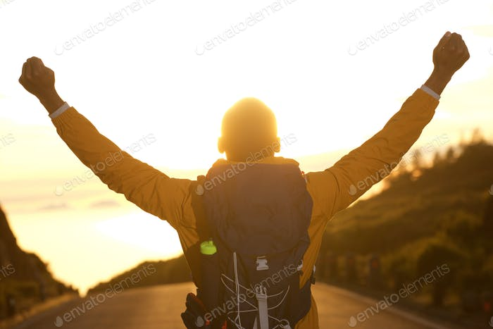 behind of hiker with arms raised during sunset