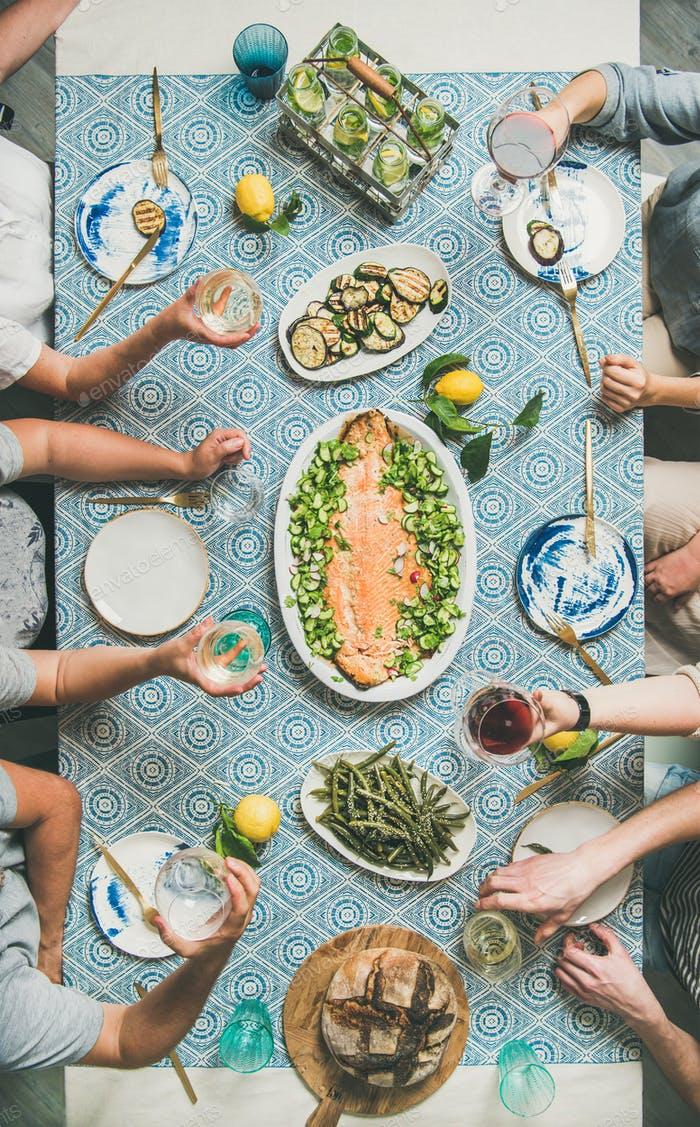 Mediterranean style dinner with cooked salmon, bread, lemonade, vertical composition