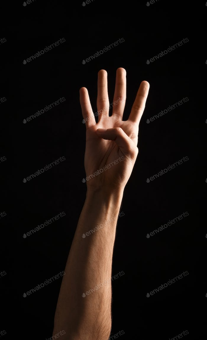 Male hand shows number four isolated at black