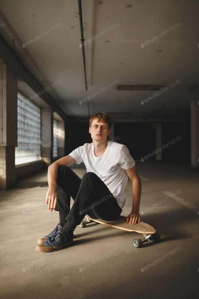 Portrait of cool boy with brown hair sitting on skateboard and dreamily looking in camera