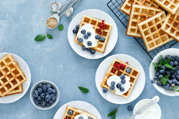 Traditional belgian waffles with cream cheese and fresh blueberry on blue background, top view