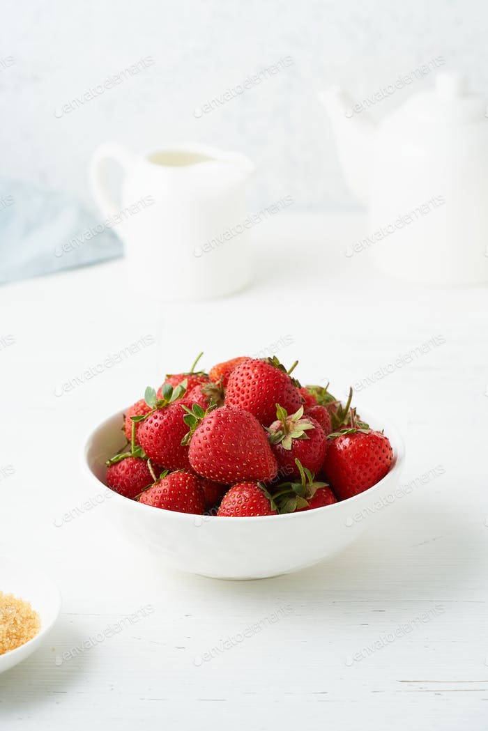 Strawberries in white bowl, on white table, morning Breakfast, summer food