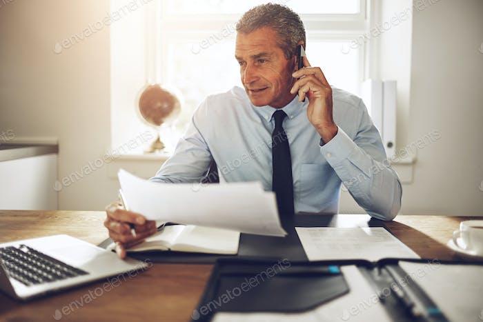 Berater sitzt an einem Schreibtisch über Papierkram am Telefon